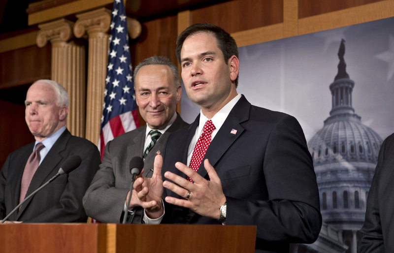 Sen. Marco Rubio, R-Fla., right, answers a reporter's question as a bipartisan group of senators propose a sweeping reform of the nation's immigration laws on Monday. With him at the Capitol in Washington are, from left, Sen. John McCain, R-Ariz., and Sen. Charles Schumer, D-N.Y.