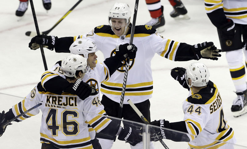 Boston's David Krejci gets a hug from Nathan Horton as Dougie Hamilton approaches after he assisted on Krejci's game-winning goal in Boston's 5-3 win over Carolina.