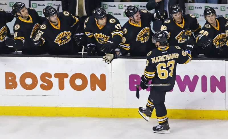 Brad Marchand of the Boston Bruins is welcomed by teammates Tuesday night after scoring a shootout goal that proved the winner against the Devils.