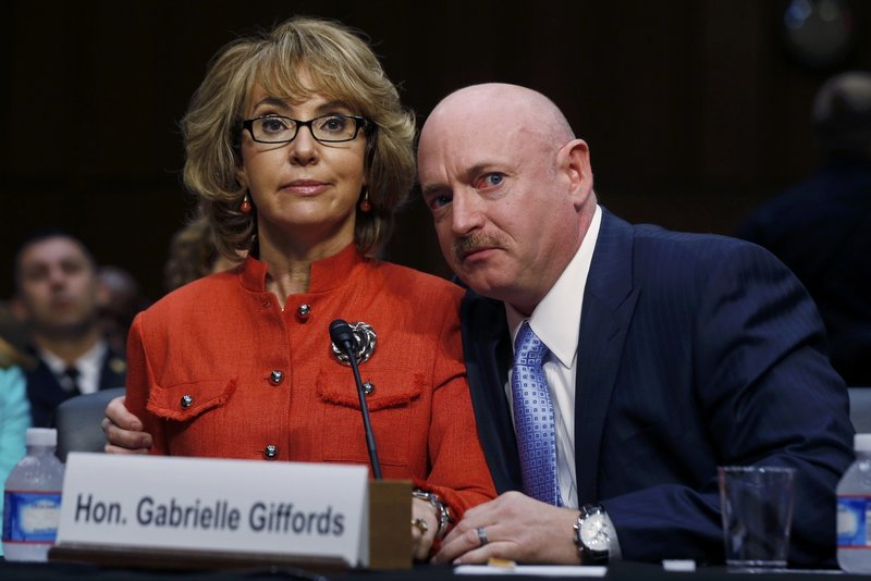 Former U.S. Rep. Gabrielle Giffords, flanked by her husband, Mark Kelly, delivers her opening remarks Wednesday at a Senate Judiciary panel hearing about guns and violence.
