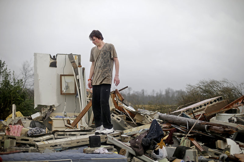 Will Carter, 15, discovers extensive damage to his house after arriving home from school following a tornado that touched down Wednesday in Adairsville, Ga.