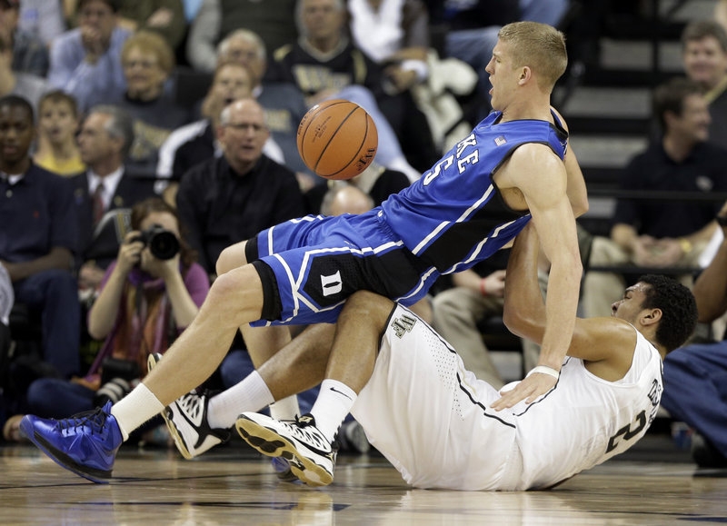 Mason Plumlee of Duke falls on top of Wake Forest's Devin Thomas in Wednesday's game at Winston-Salem, N.C. Plumlee had 32 points in Duke's 75-70 win.