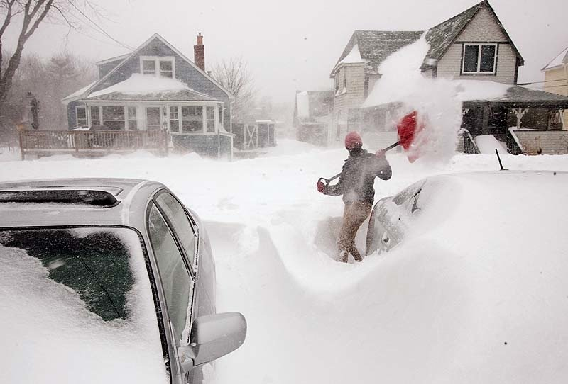 Julia May digs buried cars from the snow in her driveway on West Grand Avenue in Ocean Park on Saturday.