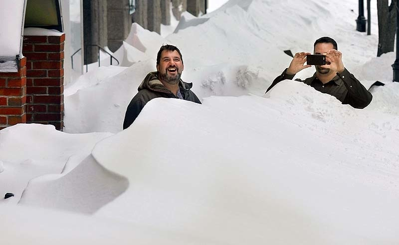 Adrian Gusteau, left, chef at the Old Port Tavern, and Jason Bisbing, right, bartender, step outside to marvel at the mounds of snow on the sidewalks of Moulton Street on Saturday afternoon in the aftermath of a blizzard that dumped more than 30 inches of snow on downtown Portland.