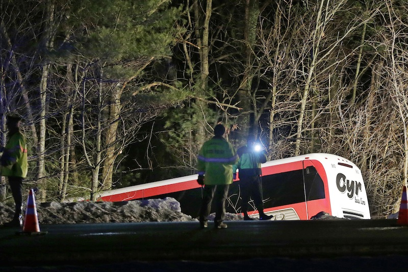 Police work at the scene of the bus crash in Georgetown, Mass., on Tuesday that injured the bus driver and seven players and two coaches from the University of Maine women's basketball team.