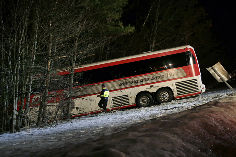 Police work at the scene in Georgetown, Mass., on Tuesday where a bus carrying University of Maine women's basketball players crashed on Interstate 95 north of Boston.