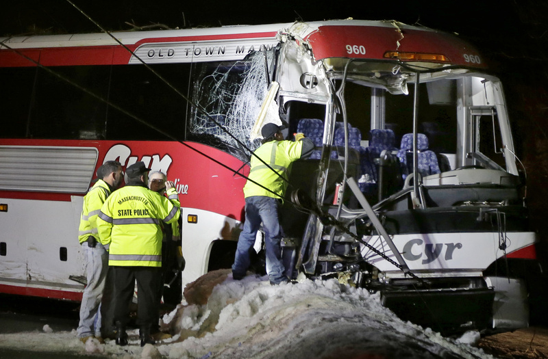 Massachusetts State Police examine the front of a bus that crashed in Georgetown, Mass., on Tuesday while carrying University of Maine women's basketball players to a game.