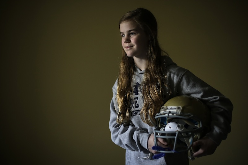 Caroline Pla, 11, poses for a photograph with her helmet Thursday, Feb. 21, 2013, in Doylestown, Pa. Pla is fighting the Roman Catholic Archdiocese of Philadelphia for the right to continue playing church sponsored youth football. (AP Photo/Matt Rourke)