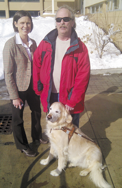 Bruce Archer of Presque Isle, right, his Seeing Eye dog Flash, and Kristin Aiello, an attorney with the Disability Rights Center who represented Archer in the discrimination complaint he filed with the Maine Human Rights Commission.