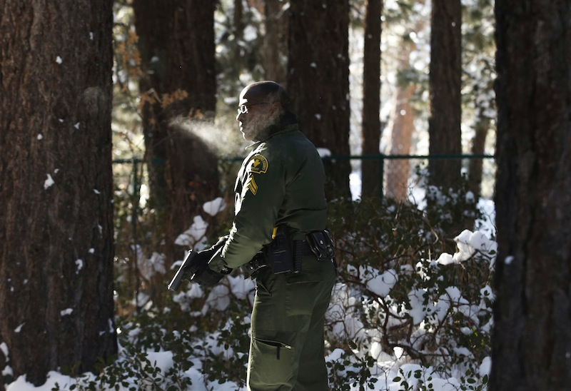 San Bernardino County Sheriff's officer Ken Owens searches a home for former Los Angeles police officer Christopher Dorner in Big Bear Lake, Calif, Sunday, Feb. 10, 2013. The hunt for the former Los Angeles police officer suspected in three killings entered a fourth day in snow-covered mountains Sunday, a day after the police chief ordered a review of the disciplinary case that led to the fugitive's firing and new details emerged of the evidence he left behind. (AP Photo/Jae C. Hong)