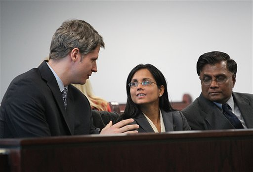Former state lab chemist Annie Dookhan, center, speaks with her lawyer Nick Gordon, left, at Middlesex Superior Court as she waits for her for arraignment to begin with her father, Rasheed Khan, on Jan. 9, 2013, in Woburn, Mass. She is charged in connection with altering drug evidence during the testing process and obstructing justice.