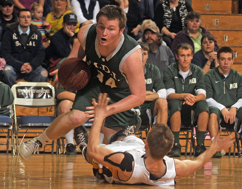 Medomak Valley's Brandon Soper, 11, draws the offensive foul from MDI's Ben Walls in the third quarter of the Eastern Class B championship game at the Bangor Auditorium Saturday. Medomak Valley won, 56-50.