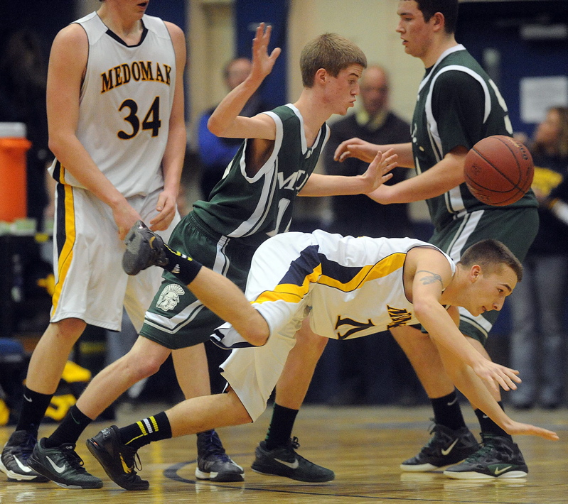 MDI's Jonathan Phelps, 10, fouls Medomak Valley's Brandon Soper, 11, in the final minutes of the Eastern Class B championship game at the Bangor Auditorium on Saturday.