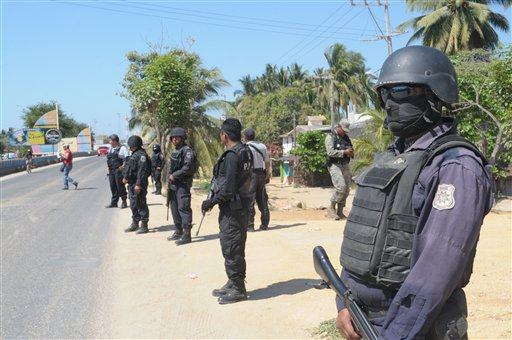 State police stand Tuesday at a roadblock in Acapulco, Mexico, implemented as part of stepped-up security efforts after masked armed men broke into a beach home, raping six Spanish tourists who had rented the house.
