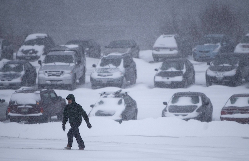 A man battles fierce winds as he climbs a hill after leaving his car in a parking lot to avoid being towed during a parking ban, Friday, Feb. 8, 2013, in Portland, Maine. (AP Photo/Robert F. Bukaty)