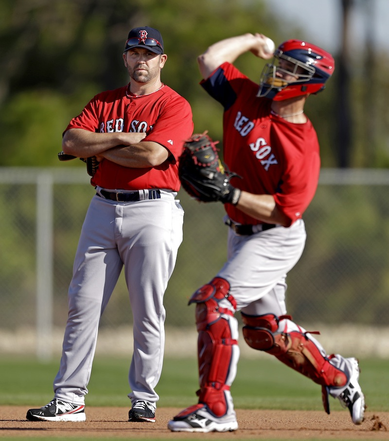Former Boston Red Sox catcher and captain and now special assistant to the team, Jason Varitek, left, watches as catcher David Ross throws during a spring training baseball workout, Wednesday, Feb. 20, 2013, in Fort Myers, Fla. (AP Photo/David Goldman)