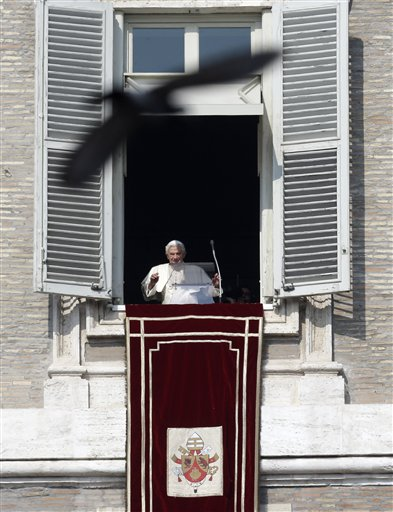 A pigeon flies in front of Pope Benedict XVI as he waves to the faithful during the Angelus noon prayer he celebrated from the window of his studio overlooking St. Peter's Square on Sunday.