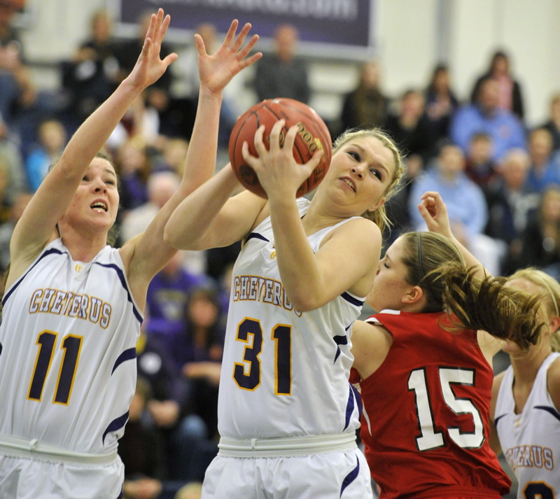 Cassidy Grover of Cheverus pulls in a rebound in front of teammate Mikayla Mayberry and Sanford's Shelby Paiement during their Western Class A girls' basketball quarterfinal at the Portland Expo. Cheverus won, 31-26.