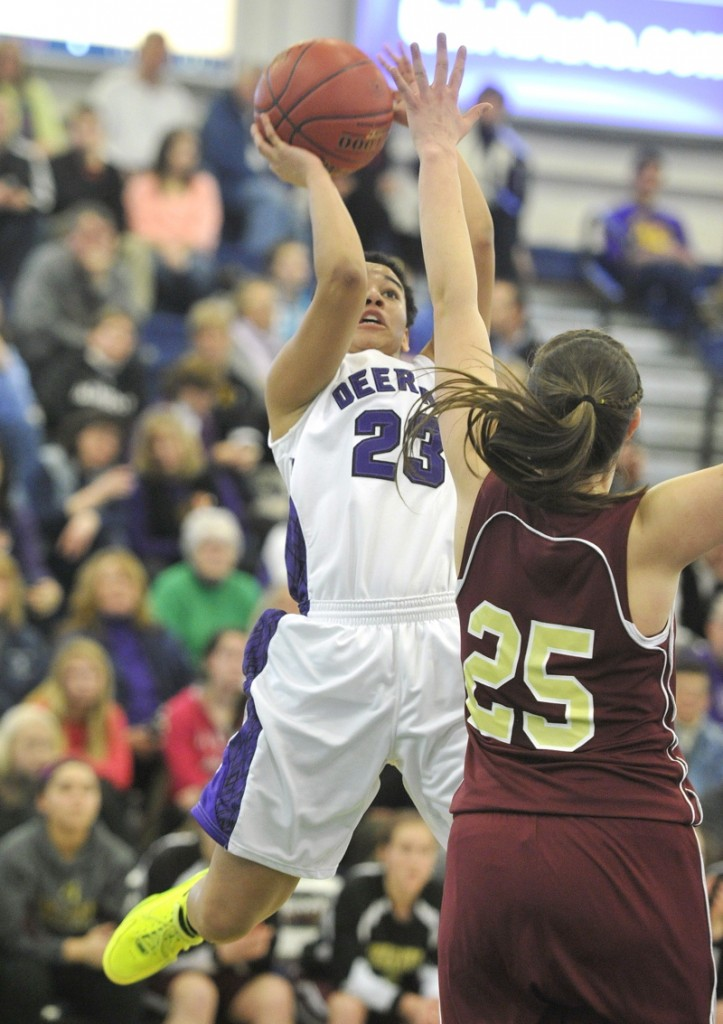 Keneisha DiRamio of Deering pulls up for a jumper over Thornton Academy's Olivia Shaw during their Western Class A quarterfinal Monday at the Portland Expo. Deering advanced with a 33-25 win.
