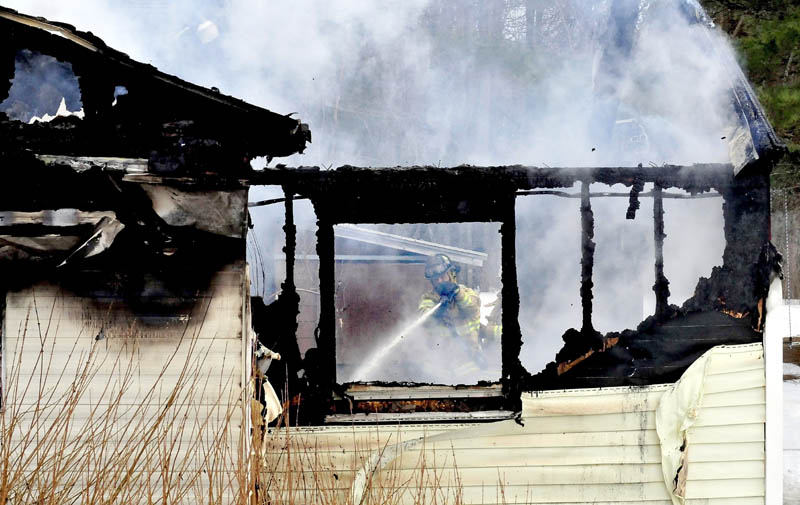 A firefighter can be seen through burned out windows and walls while fighting a fire that destroyed a mobile home Tuesday in Sidney, Maine.