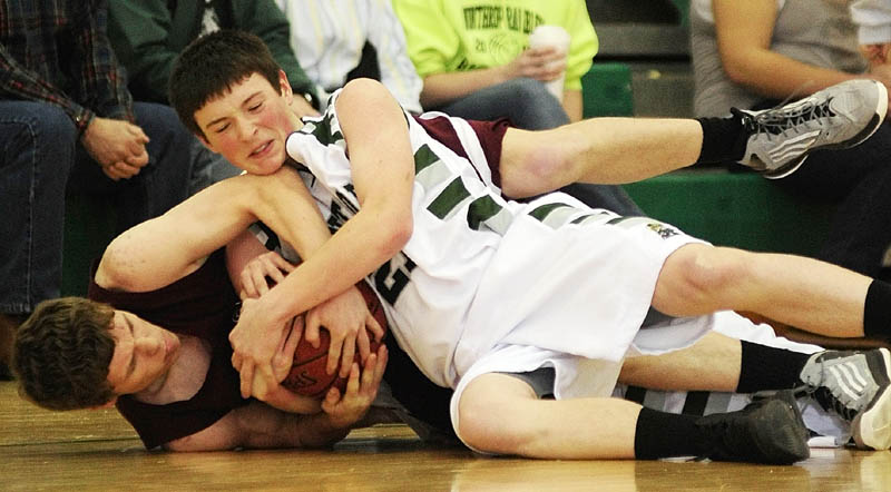 FIGHT FOR THE BALL, TRIP TO AUGUSTA: Monmouth Academy's Drew McFarren, left, and Winthrop's Matt Sekerak wrestle for a loose ball during a Western C prelim game Wednesday at Winthrop High School.