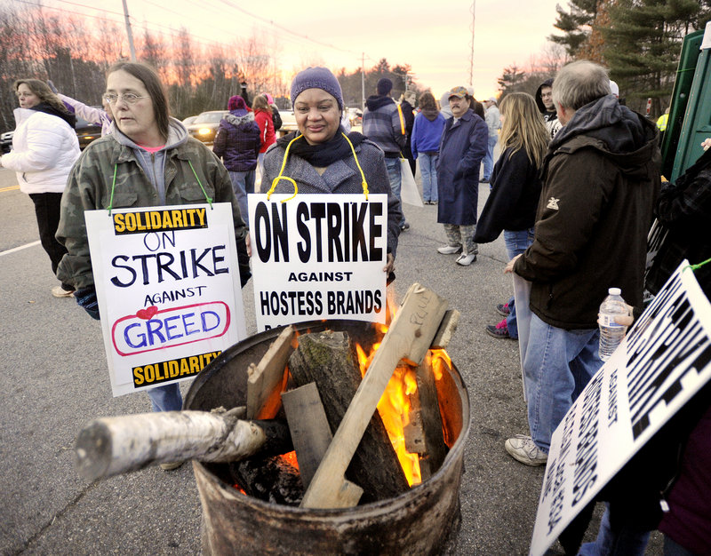 Photo by John Ewing/staff photographer... Striking Hostess Brands workers in Biddeford warm up at a fire barrel while walking on the picket line in this November 15 2012 file photo. About 370 workers at the company's bakery in Biddeford lost their jobs when the plant closed last November.