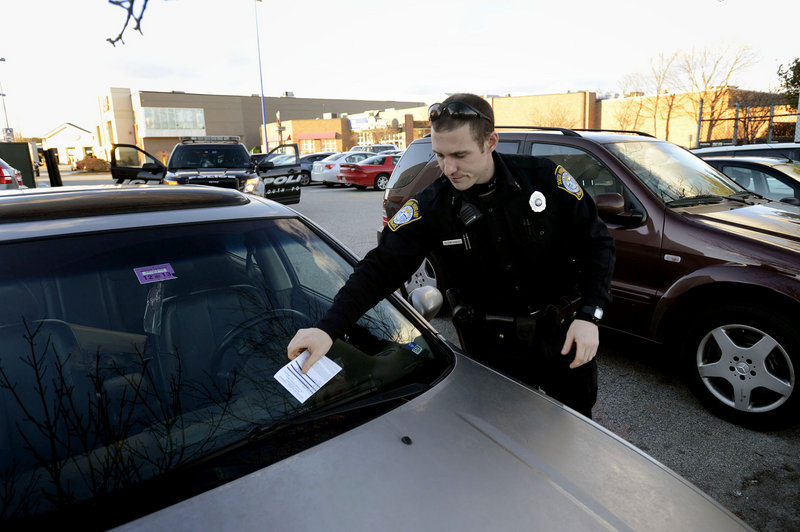 South Portland Police Officer Kevin Sager writes tickets to illegally parked cars at the Maine Mall on Thursday, Jan. 31, 2013.