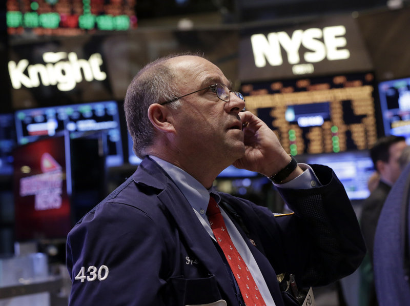 Trader Frederick Reimer works the floor of the New York Stock Exchange on Friday where a board, above, shows the closing number for the Dow Jones industrial average, which topped 14,000 for the first time since 2007. Large investors are behind the index's recent rise.
