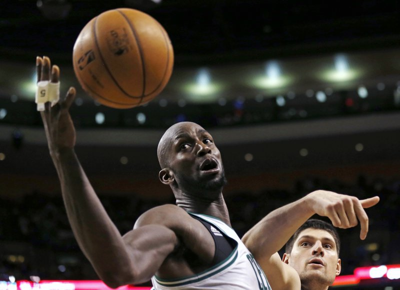 Kevin Garnett of the Boston Celtics reaches the ball ahead of Nikola Vucevic of the Orlando Magic during the second half of the Celtics' 97-84 victory at home Friday night.