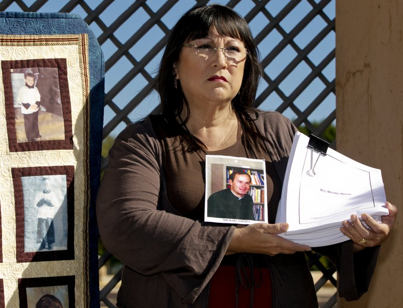 Esther Miller, 54, who says she was abused by the Rev. Michael Nocita, seen in middle picture, holds newly released files on Nocita, at a news conference Friday held by the Survivors Network of those Abused by Priests outside the Cathedral of Our Lady of the Angels in Los Angeles.
