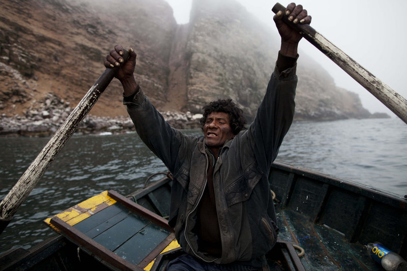 Alvaro rows a small boat as he goes fishing for the depleted anchovy in the Pacific off the coast of Peru.