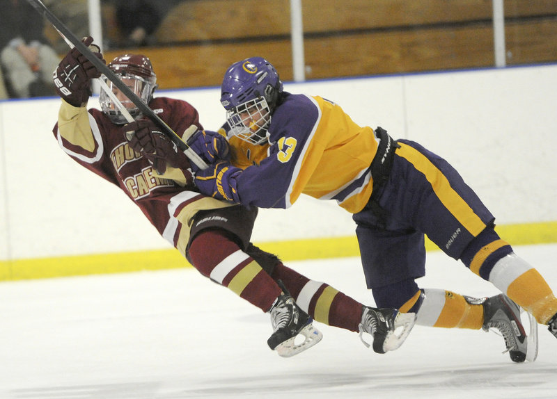 Thornton Academy's Cooper O'Brien goes down following a check by Cheverus' Andrew MacGillivray during Thursday night's high school hockey game at the Portland Ice Arena, won by Cheverus, 3-2.