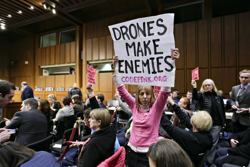 Protesters opposed to drone strikes by the CIA disrupt the start of the hearing.