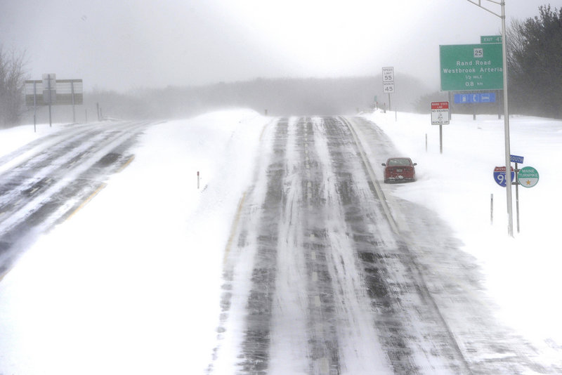 An abandoned vehicle sits on the side of the southbound lane of the Maine Turnpike in Portland on Saturday. Officials discouraged travel on the highway during the 2013 Blizzard that hit Maine.