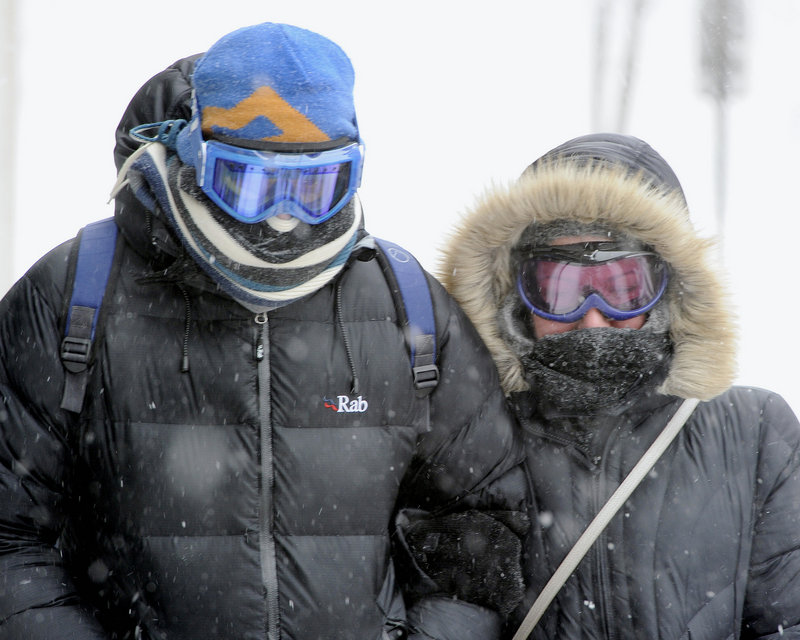 Scarves and goggles were popular Saturday as Kevin Phillips and Katie Nimmo keep their heads down into the wind as they search for an open pub in the Old Port in Portland during the Blizzard of 2013.