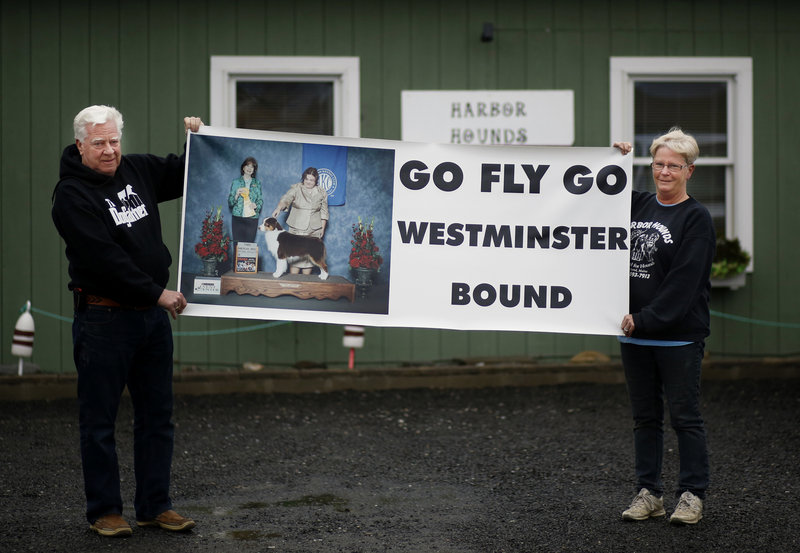 Vern Clark and his wife, Clara Gardner, hold a poster for their Australian shepherd Fly at their kennel in Rockland.