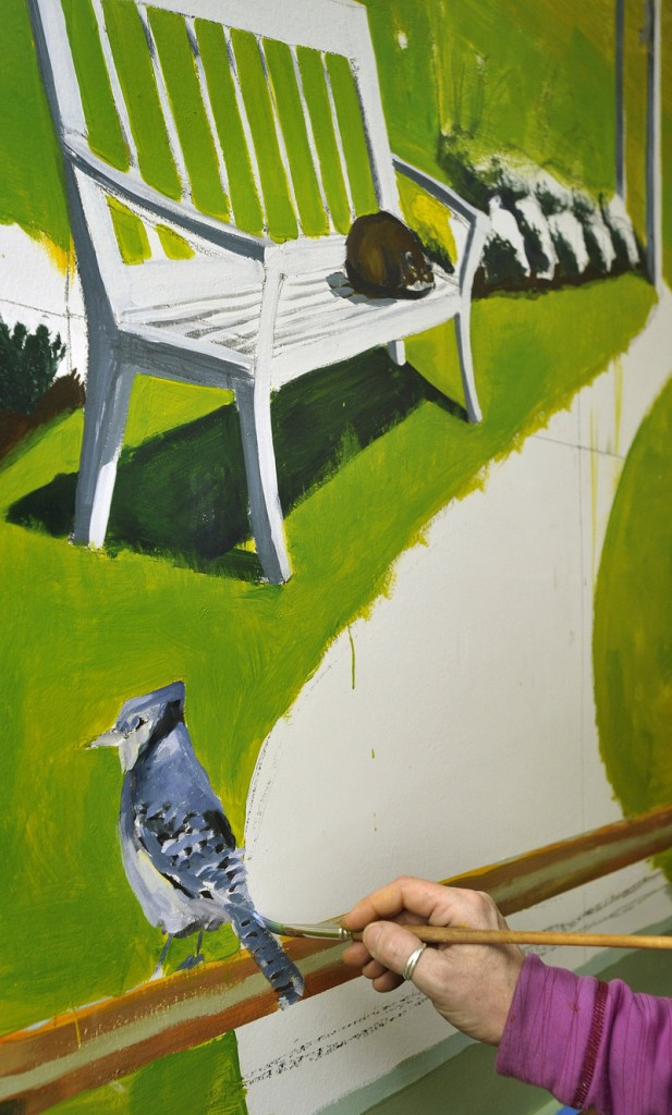Artist Francine Schrock paints a blue jay on a section of her mural.
