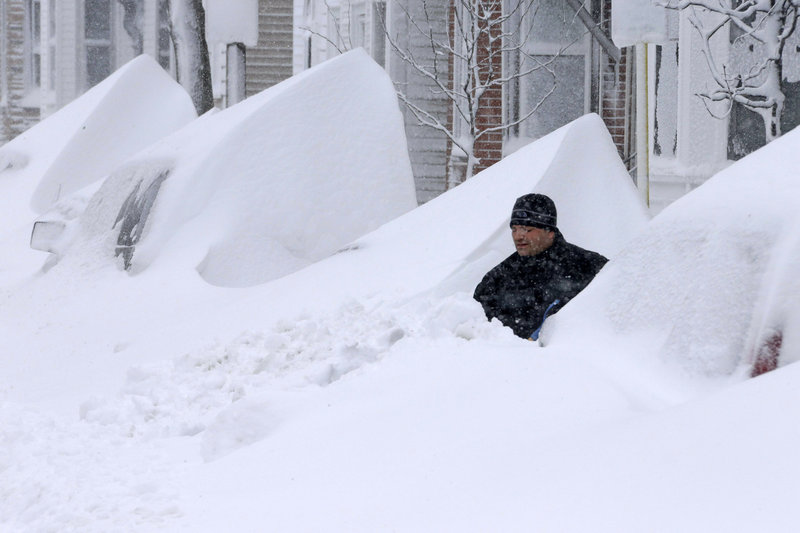 John Silver shovels snow between buried cars in front of his home on Third Street in South Boston on Saturday.