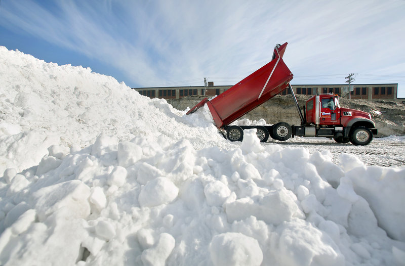 A truck dumps a load of snow in a lot at Preble and Kennebec streets in Portland on Sunday during the cleanup in the aftermath of the weekend blizzard that set a record of 31.9 inches of snowfall in the city.
