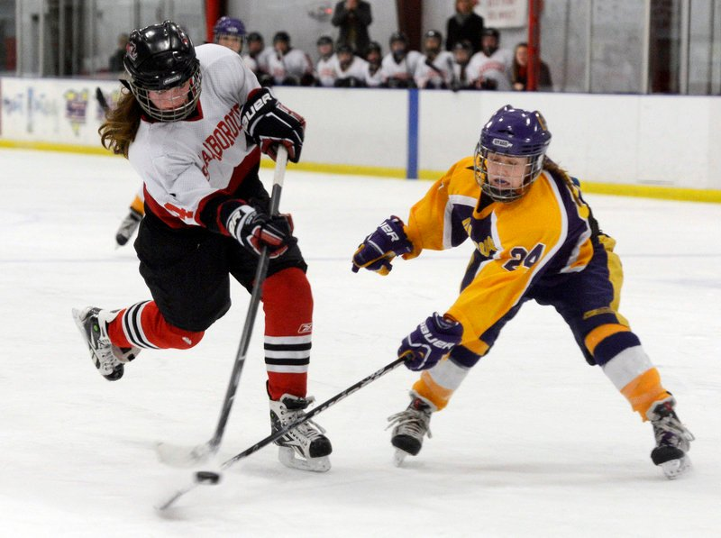 Scarborough's Kristen Murray fires the puck despite obstruction from Cheverus defender Paige Severance during Monday's Western Class A semifinal game in Saco, won by the Red Storm, 6-1.