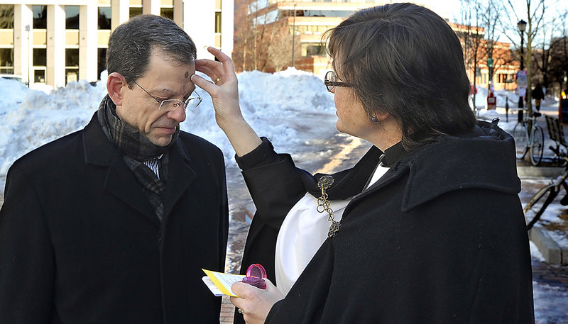 Mike Watson of Cape Elizabeth gets ashes from Suzanne Roberts, a deacon at St. Luke's, on Ash Wednesday in Portland's Monument Square.