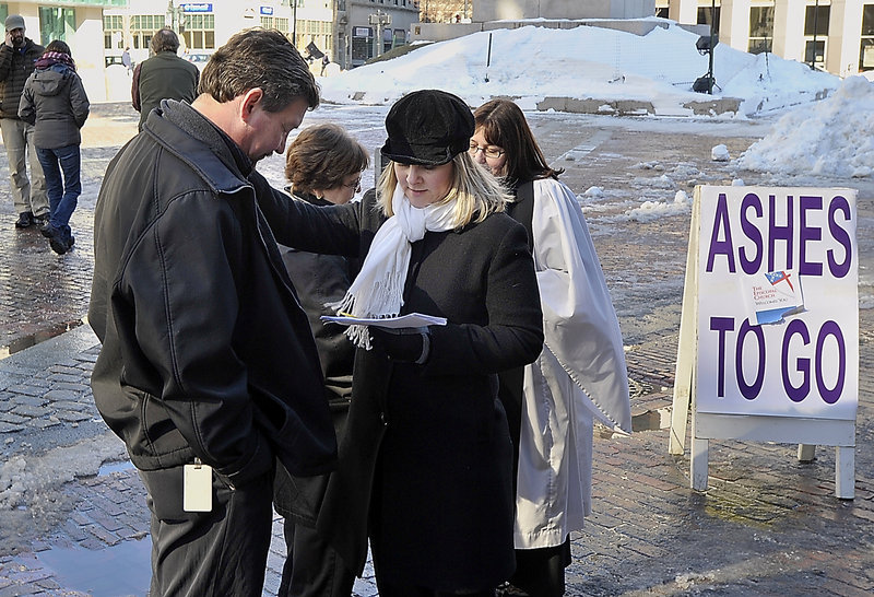 Randy LeShane of Windham and his mother, Gale Murphy, get ashes Wednesday from Gwen DeCicco, a lay person at the Cathedral Church of St. Luke in Portland, and Nina Pooley, a rector at St. Bartholomew's Episcopal Church in Yarmouth.