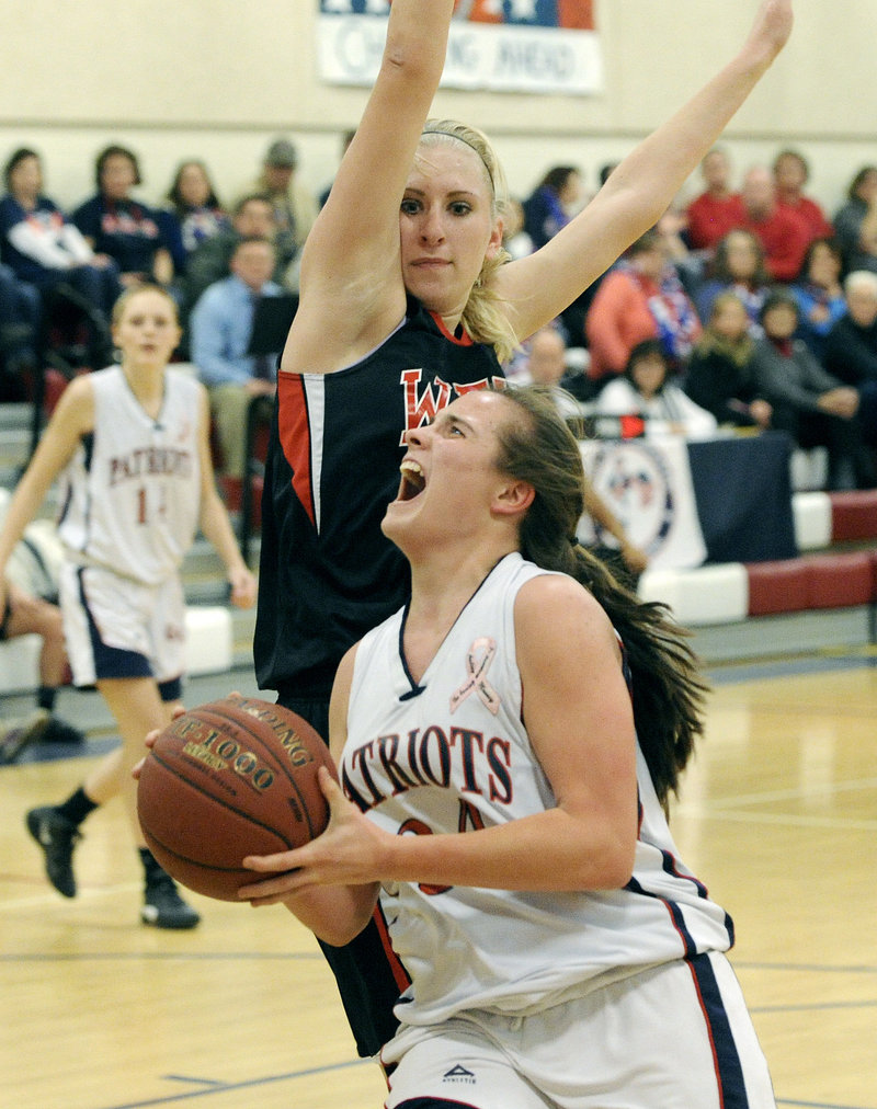 Maria Valente of Gray-New Gloucester concentrates on the basket Wednesday night while driving against Alison Furness of Wells during their Western Class B prelim. Wells won 53-46 and will meet Spruce Mountain in a quarterfinal.