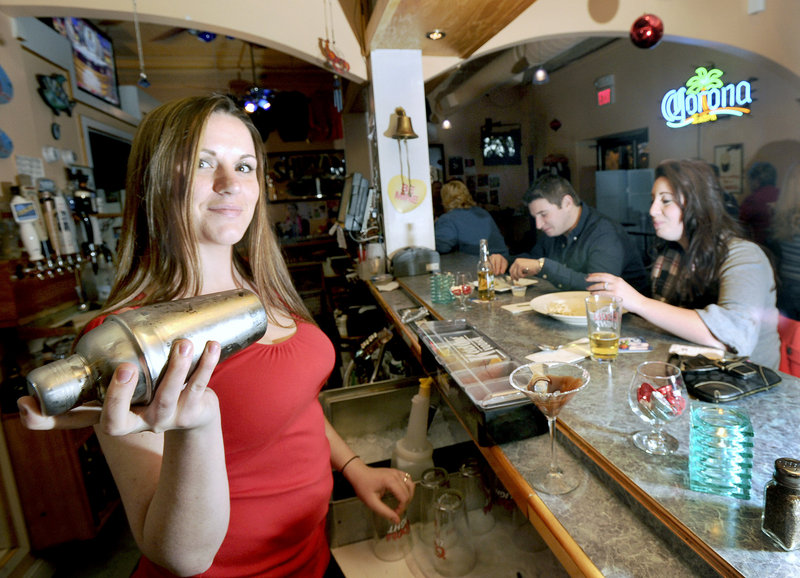 "JJ's Eatery Too bartender Kristen Keenan shakes a ""chocolate-covered pretzel martini"" while Sam Maddams and Lauryn Goyet dine at the bar in Old Orchard Beach."