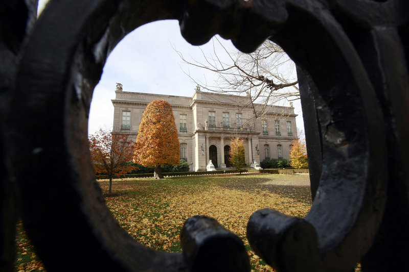 Rhe Elms mansion in Newport, R.I., seen through an opening in an iron fence.