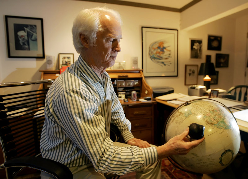 Former Apollo astronaut Rusty Schweickart holds a model of an asteroid over a globe in 2005 to demonstrate the devastation such an impact would have.
