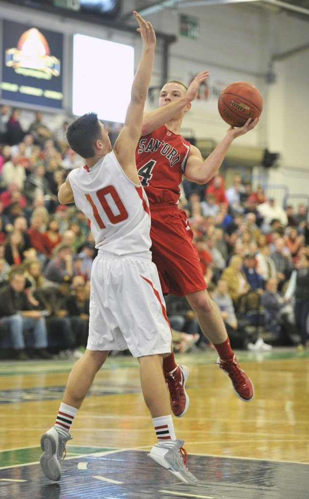 Calvin Carr of South Portland applies tight pressure, forcing Ryan Camire of Sanford into an off-balance shot Friday night.