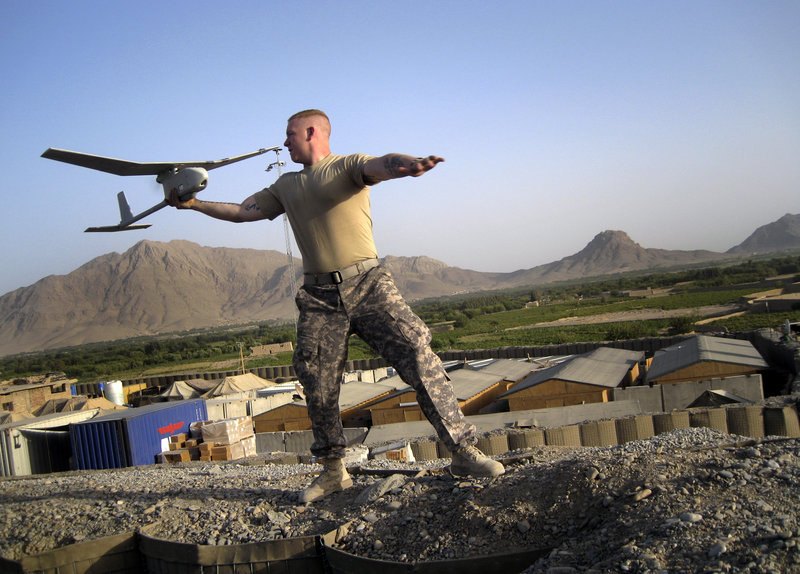 "Pfc. Joseph Robinson of Eugene, Ore., launches a ""Raven,"" an unmanned reconnaissance drone, at Combat Outpost Senjeray, Kandahar province, Afghanistan, on Sept. 11, 2010."