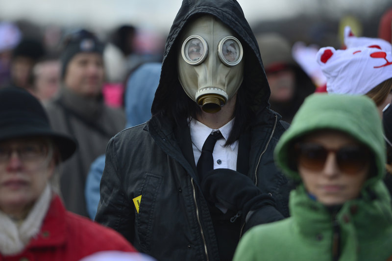 "A man wearing a gas mask joins the crowd gathered Sunday on the National Mall in Washington for the ""Forward on Climate"" rally."