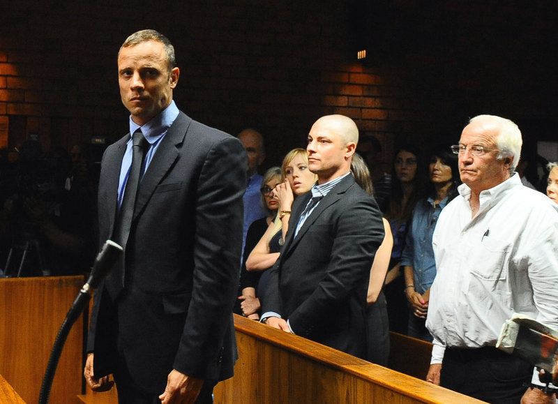 Oscar Pistorius, foreground, stands Tuesday following his bail hearing, in Pretoria, South Africa. He said he shot Reeva Steenkamp after mistaking her for an intruder.